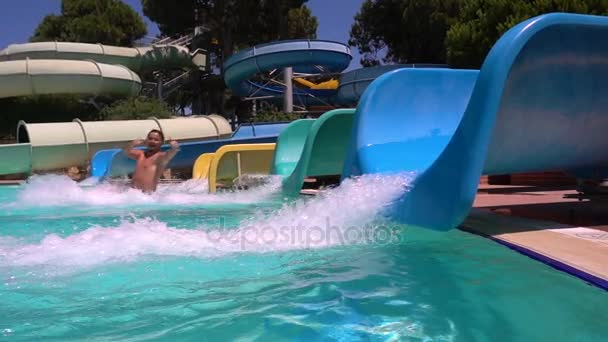 A woman and a man descend from water slide. Smiling at camera. Aquapark. Slow motion.