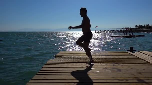 Člověk je skákání z mola do moře. Skok z mostu do moře. Skoky do moře. Zpomalený pohyb