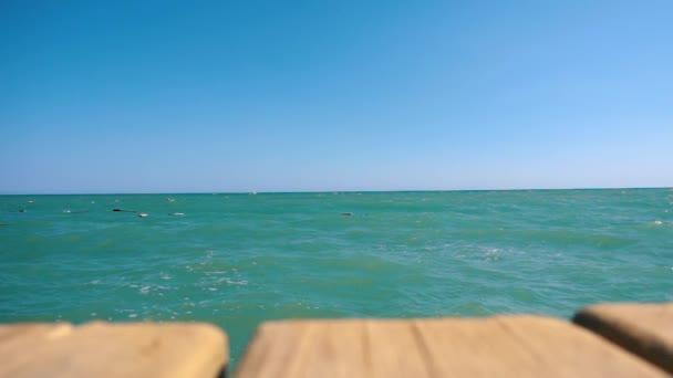 Člověk je skákání z mola do moře. Vodu. Skok z mostu do moře. Skoky do moře. Letní dovolená v hotelu na pobřeží Černého moře v Turecku. Zpomalený pohyb