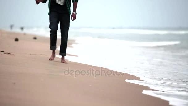Muž k fotoaparátu na pláži