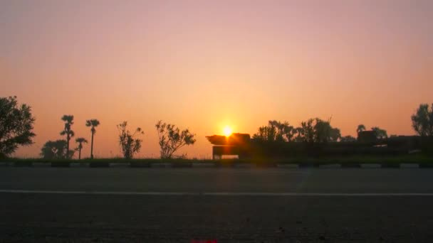 transporting semi trucks driving on busy highway at beautiful golden sunset in summer. Sunrise over highway