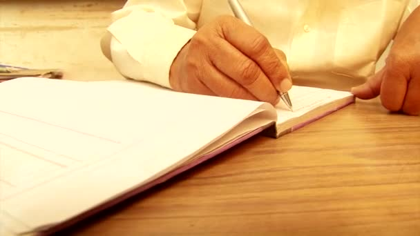 Close up old man writing notes in notebook.