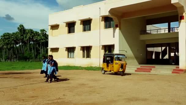 Tiruppatur, Indie - 18. února 2015: School Girls Walking domů ze školy u budovy školy, Indie