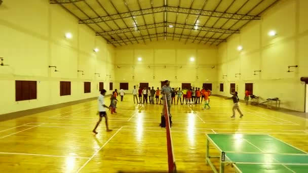 TIRUPPATUR, INDIA - OCTOBER 10th, 2014: Young students learns to play badminton with her coach in a badminton court
