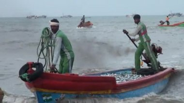 POOMPUHAR, INDIA - NOVEMBER 12, 2015: Fishers pull out baskets of fish from the boat and sort it into boxes.