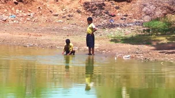 Madurai, Indien - 20. April 2015: Zoom, Aufnahme von zwei Kinder spielen am Wasser-Teich