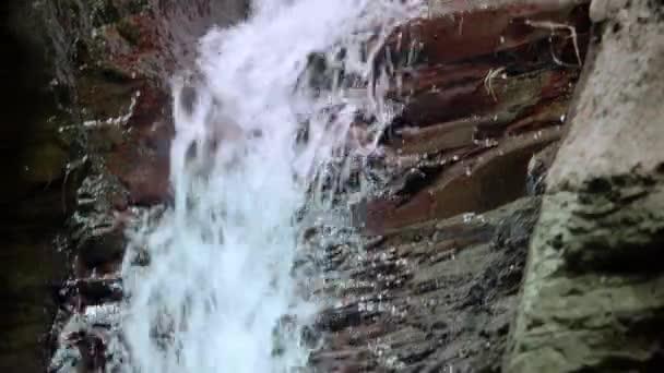 Vodopád se valí přes velké skály v lese