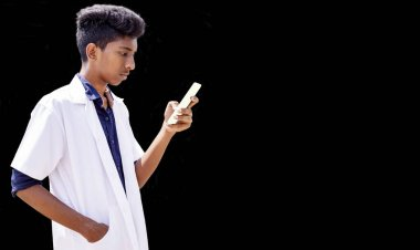 Closeup photo of man doctor standing isolated on black background looking at screen of cellphone.