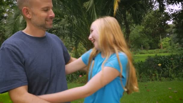 A father and daughter hug outside in nature - slowmo handheld