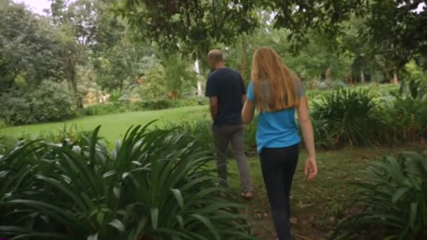 A father and daughter walking through a park together- slowmo steadicam