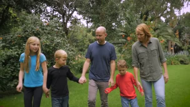 A friendly family walking barefoot through the grass holding hands - slowmo