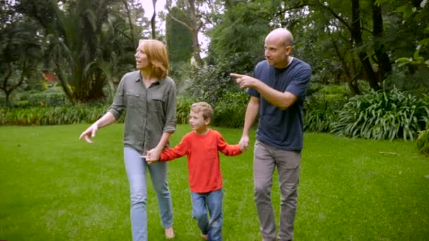 A mother and father hold hands with their son and point out things - slowmo