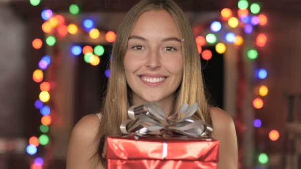 Nádherná mladá žena vydrží dar, zatímco konfety padá na ni