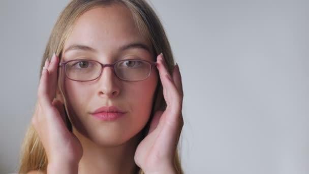 Vonzó fiatal nő megpróbálja a szemüvegek és mosolyog