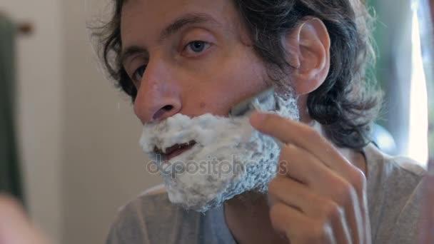 Muž začíná holení jeho plnovous s holicí strojek