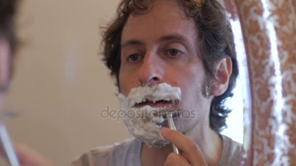 Reflexe člověka pomocí holicí strojek oholí vousy-dolly