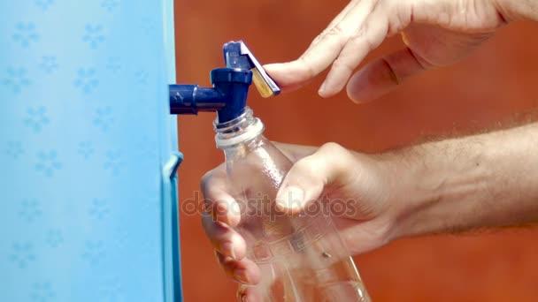 Egy ember Újratöltés egy műanyag üveg vizet a víz hűtő
