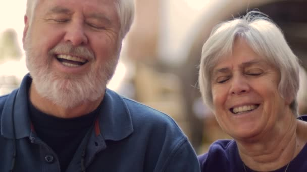 An attractive elderly couple smiling and laughing sitting outside