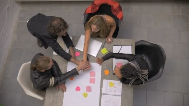 A diverse group of millennials celebrate success at a meeting - overhead slowmo
