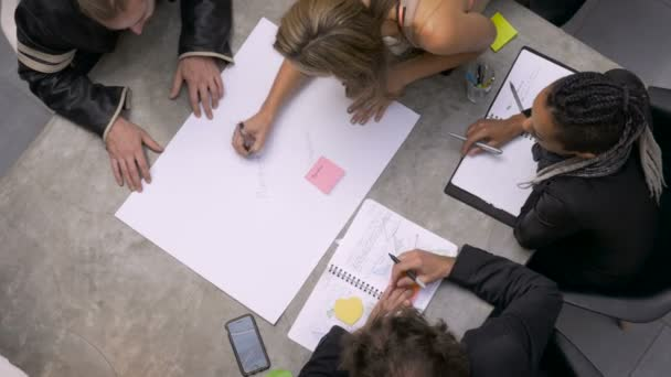 Two women write down their ideas during a brainstorming session