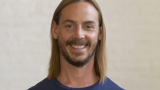 Un Hombre Milenario Con Pelo Rubio Largo Y Una Barba Sonrie A La - Pelo-rubio-hombre