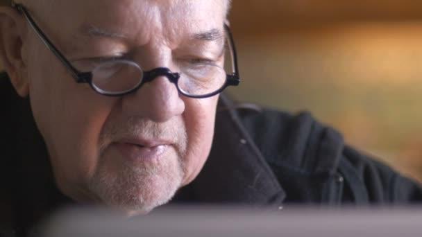Ein älterer senior Mann auf der Suche auf seinem Laptop - dolly