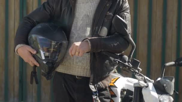 Mladý muž, který stál vedle jeho motocykl dává palec nahoru