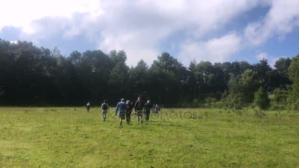 Skupina turistů den chodit v poli směrem k lesu-široké