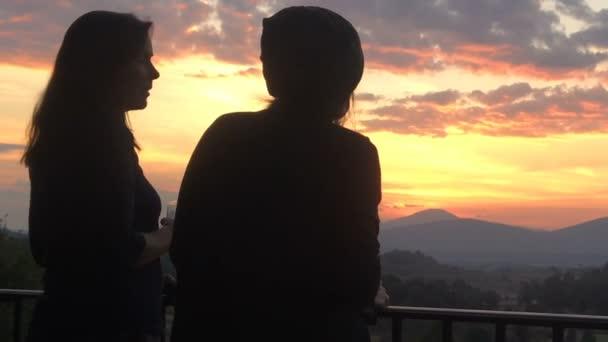 Siluety dvou žen mluví, s výhledem na barevné západ slunce v horách