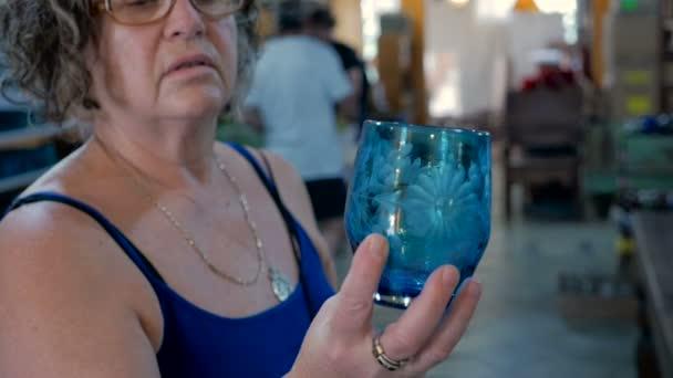 Babyboomer-Frau untersucht beim Einkaufen sorgfältig ein Glas in der Hand