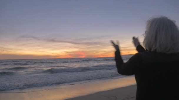 Excited happy retired fit active 60s woman clapping and enjoying sunset on beach