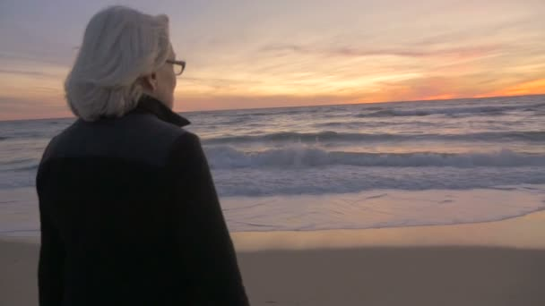 Healthy retired mature active woman looking at sunset on beach