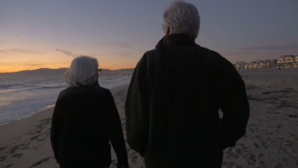 Mature fit active retired 60s couple walking on beach during sunset
