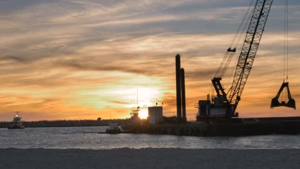 Bagger-Schiff arbeiten bei Sonnenuntergang mit Vögel fliegen im Hintergrund