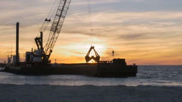 Bagger-Schiff entfernen Sand vom Meeresboden bei Sonnenuntergang