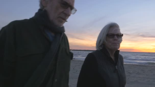 Healthy happy smiling elderly 60s couple walking on beach at sunset
