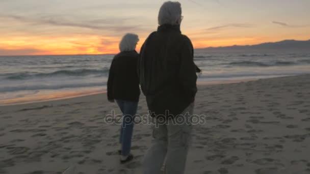 Zdravých starších 60 let pár procházky a cvičení na pláži při západu slunce