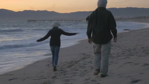 Happy mature 60s couple running and playing on the beach at sunset