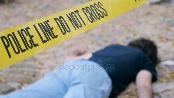 A dead body roped off with Police Line Do Not Cross tape at crime scene
