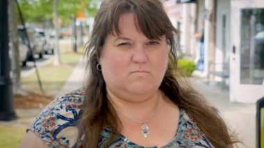 Angry, mad, and bothered obese woman standing outside giving the evil eye - CU