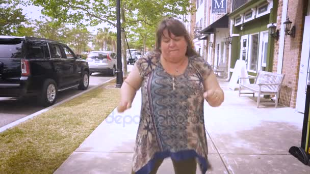 A large happy woman dancing and moving her arms around outside