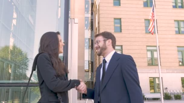 Beautiful businesswoman and businessman shaking hands and viewing smart phone