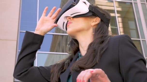 Donna di affari esamina le sue mani in un mondo di realtà virtuale attraverso gli occhiali di protezione