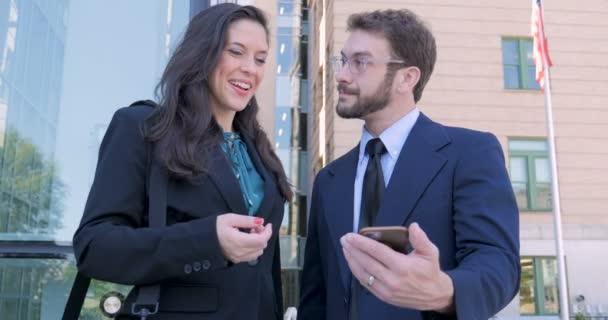 Happy usmívající se obchodní partneři při pohledu na chytrý telefon si potřást rukou a nechat