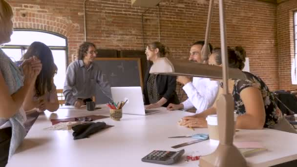 Group of creatives at a meeting laughing and celebrating a successful business