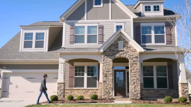 Man walks up sidewalk entrance to his generic suburban house and goes inside