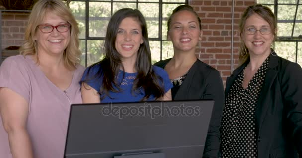 Four professional women smiling behind a computer in modern startup office