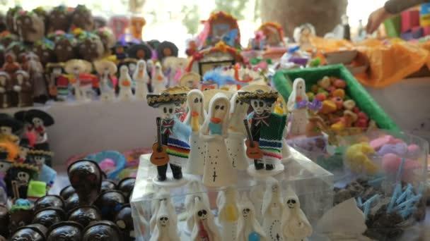 Miniatur-Süßigkeiten-Geister und Skelette auf dem Display für den Tag der Toten