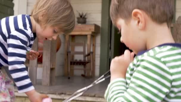 Hermano ayudando a su hermanita para colorear y pintar huevos de ...