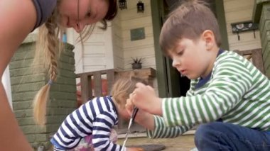A millennial mother and her two young kids dyeing easter eggs together
